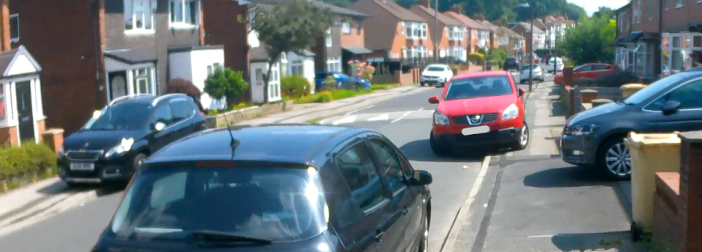 A residential street with cars partially blocking the footways on both sides of the road. A car in the foreground is parked correctly on the carriageway.