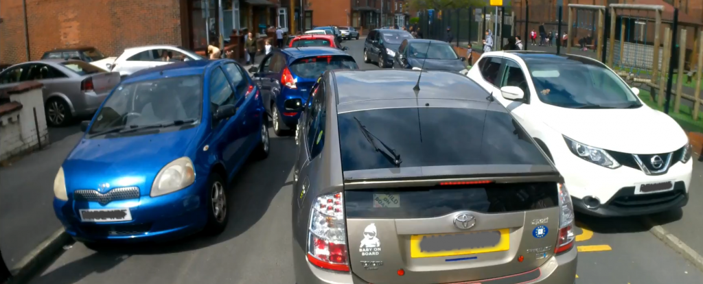 A narrow residential street with a local primary school on the right hand side. The street is full of cars being driven and parked, with some people driving their cars on the footway outside the school gates to squeeze past others.
